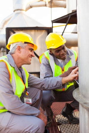 two petrochemical technicians inspecting fuel tank in plant photo