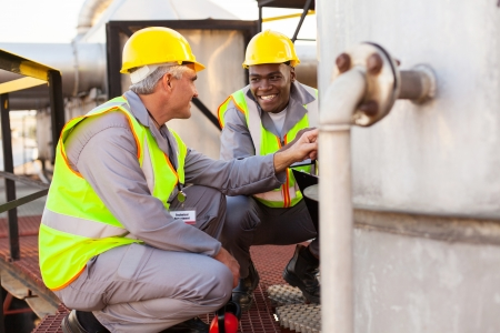 company employee: two oil chemical industry technicians working in plant