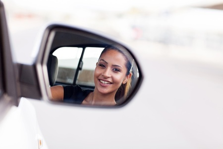 beautiful young businesswoman driver looking at side mirror photo