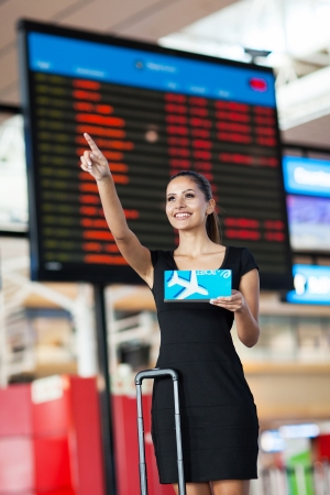 arrival departure board: cheerful busenesswoman at airport pointing in front of flight information board Stock Photo