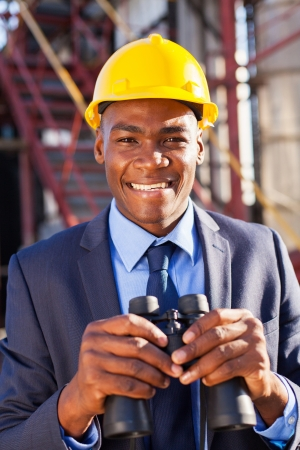 portrait of smiling african american petrochemical manager with binoculars visiting plant photo