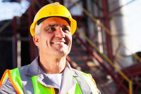 happy middle aged chemical industry worker in plant photo