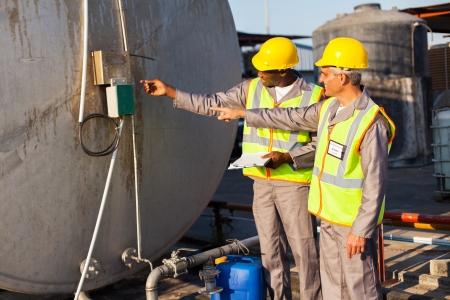 chemical plant: twee industriële ingenieurs inspectie brandstoftank in chemische fabriek