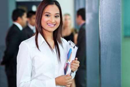 portrait of attractive secretary standing in meeting room holding a clipboard photo