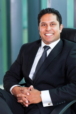 cheerful indian business man sitting in modern office photo