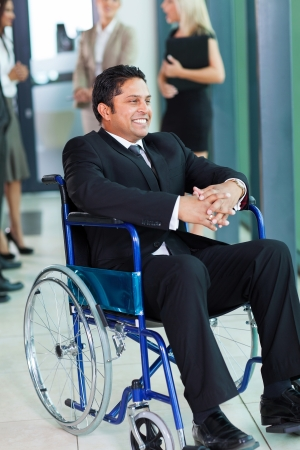 cheerful indian businessman in wheelchair with colleagues on background Stock Photo - 20782231