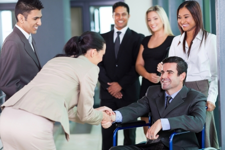 multicultural: young businesswoman greeting handicapped business partner and team