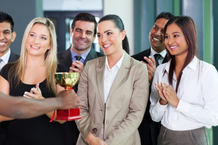 pretty businesswoman and team receiving a trophy
