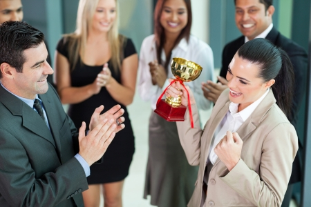 beautiful cheerful female corporate worker receiving a trophy from company CEO