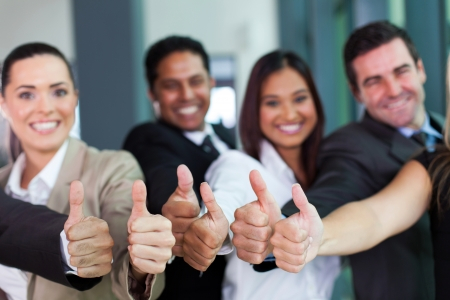 cheerful business group giving thumbs up photo