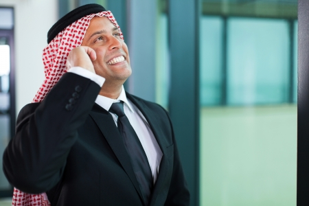 cheerful muslim businessman talking on cell phone and looking up photo