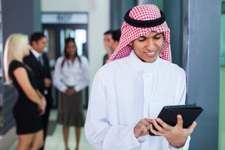 agal: saudi arabian businessman using tablet computer in modern office