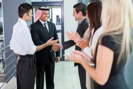 translator: translator introducing arabian businessman to business partners Stock Photo