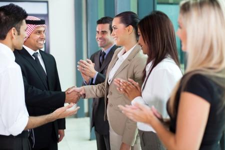 translator: young translator introducing arab businessman to group of businesspeople Stock Photo