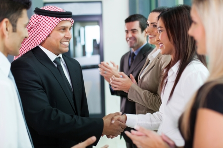 translator: cheerful group of business team welcoming arabian businessman Stock Photo
