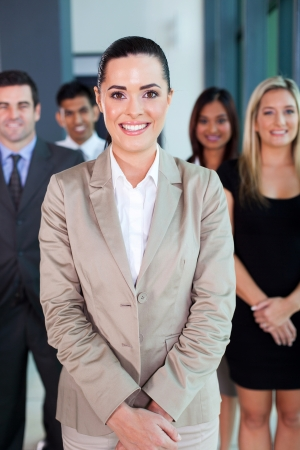 diversity people: beautiful female business leader with team standing on background Stock Photo