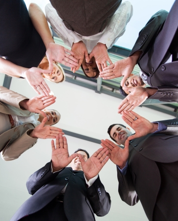 young entrepreneurs: low angle view of business team hands together in circle  Stock Photo