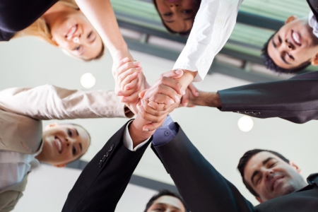 multiracial groups: underneath view of group businesspeople handshaking