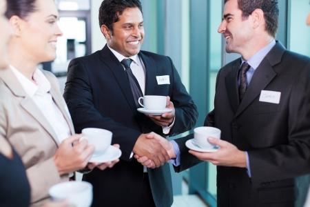 reunion de personas: hombres de negocios amigables interactuando durante las vacaciones de conferencia Foto de archivo
