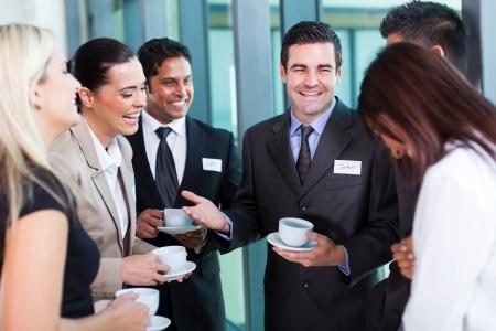 conferencia de negocios: divertido empresario contando una broma durante la pausa para el caf� de conferencias