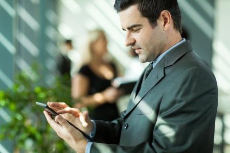 mid adult men: handsome businessman using tablet computer in modern office