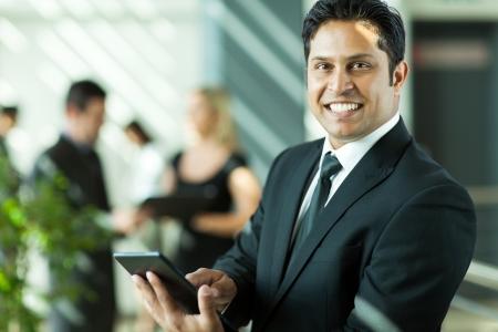陽気な若いインドのビジネスマンのオフィスでタブレット コンピューターでの作業