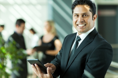 vrolijke jonge Indiase zakenman werken op de tablet-computer in het kantoor