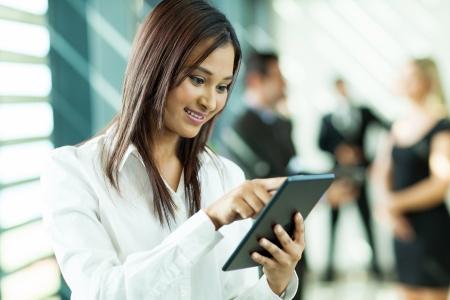 사무실에서 태블릿 컴퓨터를 사용하여 아름다운 인도의 화이트 칼라 노동자