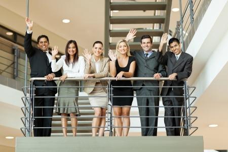 gente saludando: alegre grupo de hombres de negocios que agita en la escalera