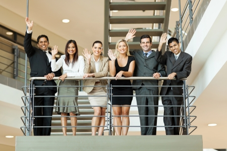 cheerful group of business people waving at stairway