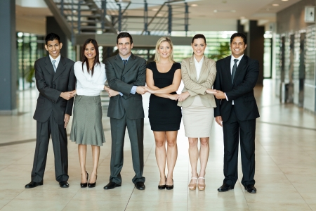 cheerful group of business people holding hands