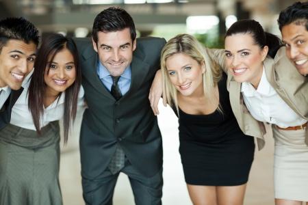huddling: cheerful group of business people huddling Stock Photo