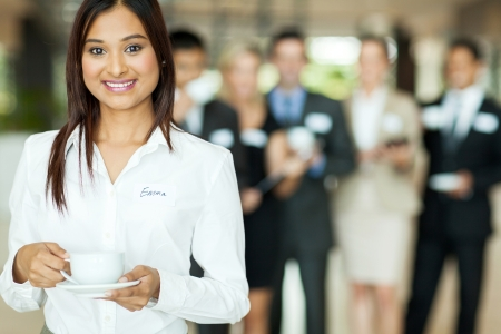 smiling indian businesswoman having coffee during conference break photo