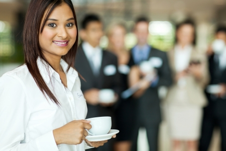 office break: beautiful young indian woman drinking coffee during seminar break Stock Photo