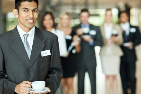 smiling young indian businessman having coffee break during seminar  photo