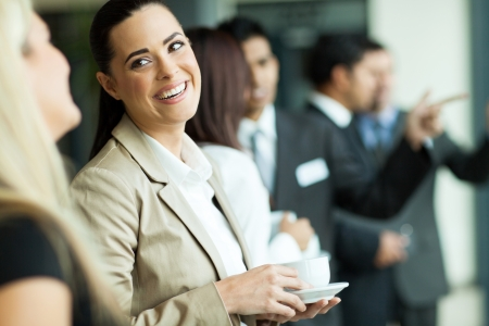 attractive businesswoman having fun conversation with colleague during break photo