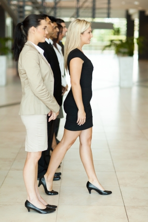 beautiful businesswoman stepping forward out of crowd photo