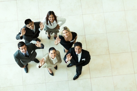 overhead view of businesspeople looking up and waving photo