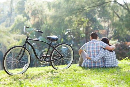 first love: back view of romantic teenage couple sitting outdoors with bicycle next to them