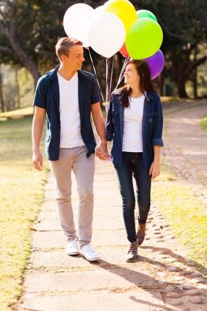 adolescencia: adorable pareja de adolescentes caminando en el parque tomados de la mano Foto de archivo