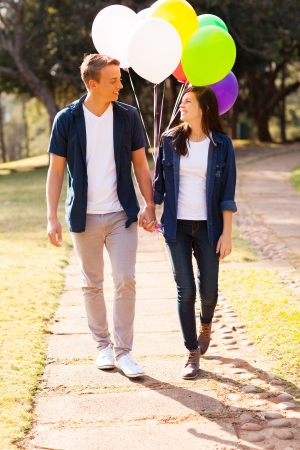 adorable teenage couple walking at the park holding hands photo