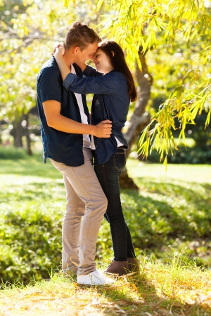 young couple hugging kissing: romantic young teenage coupe kissing in forest