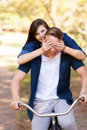 playful teen girl covering boyfriends eyes with hands while riding a bike photo