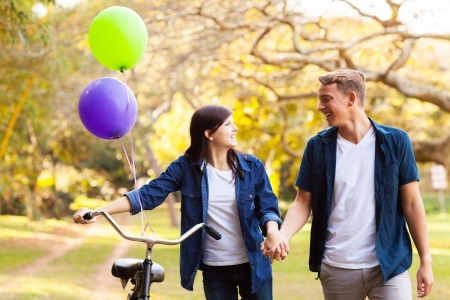 lovely couple: beautiful teenage couple walking in park holding hands