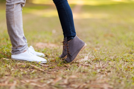 teenage couple kissing outdoors at the park photo