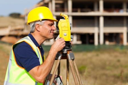 elevation meter: Senior land surveyor working with theodolite at construction site