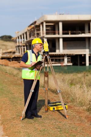 elevation meter: middle aged land surveyor working at construction site