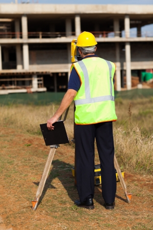 land surveyor: rear view of senior land surveyor working at construction site with theodolite