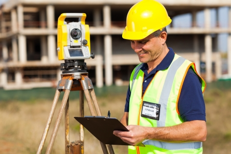 land surveyor: mid age land surveyor working at construction site with theodolite