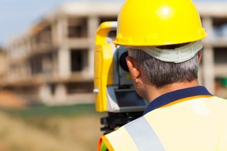 geodesist: rear view of senior land surveyor working on theodolite
